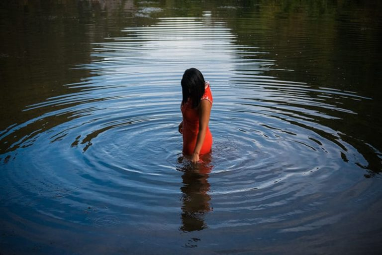 Woman in water wearing red dress with ripples