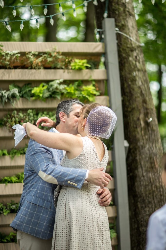 20th anniversary kiss Alisa Tongg Celebrant Family Vow Renewal at The Living Wall at Promise Ridge Jeremie Barlow Photography